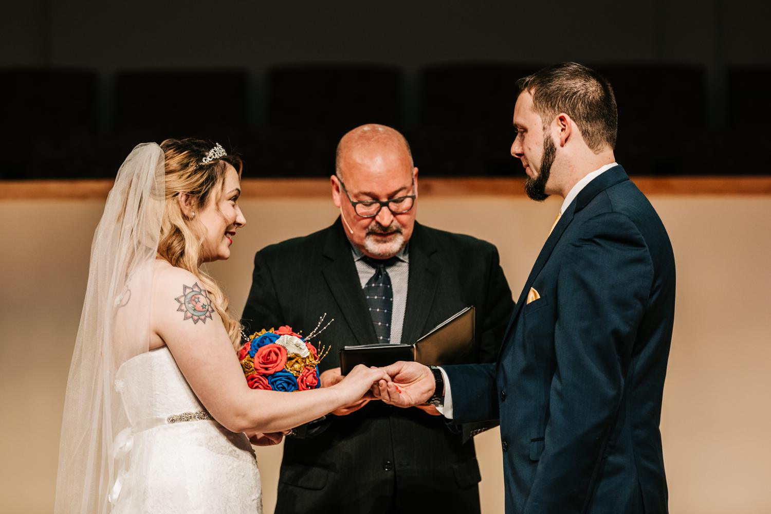 Tattooed bride and groom holding hands at altar