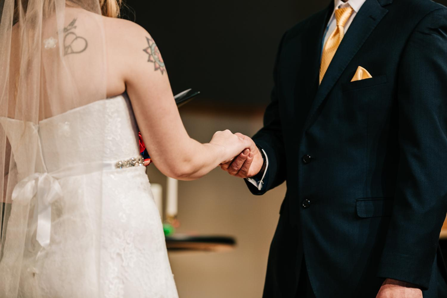 Tattooed bride and groom holding hands