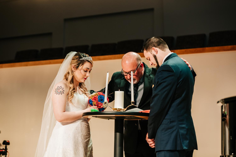 Tattooed bride and groom praying at wedding