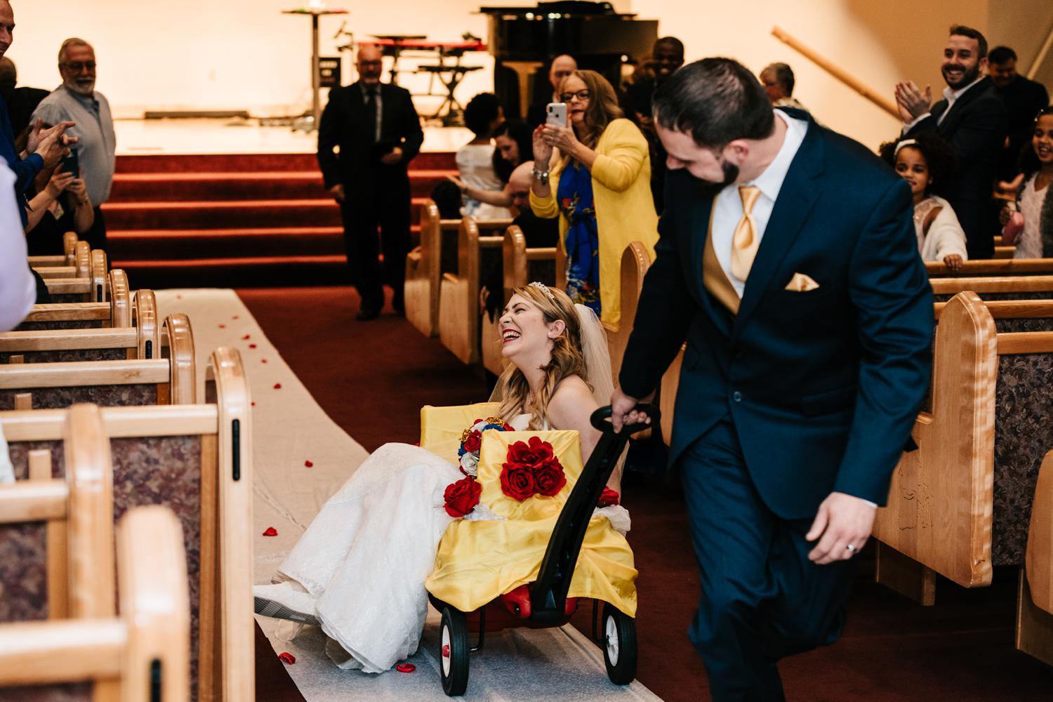 Groom pulling tattoed bride up aisle in wagon