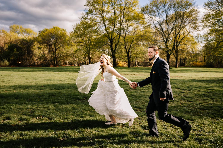 Tattoed bride and groom running through field in spring sunlight