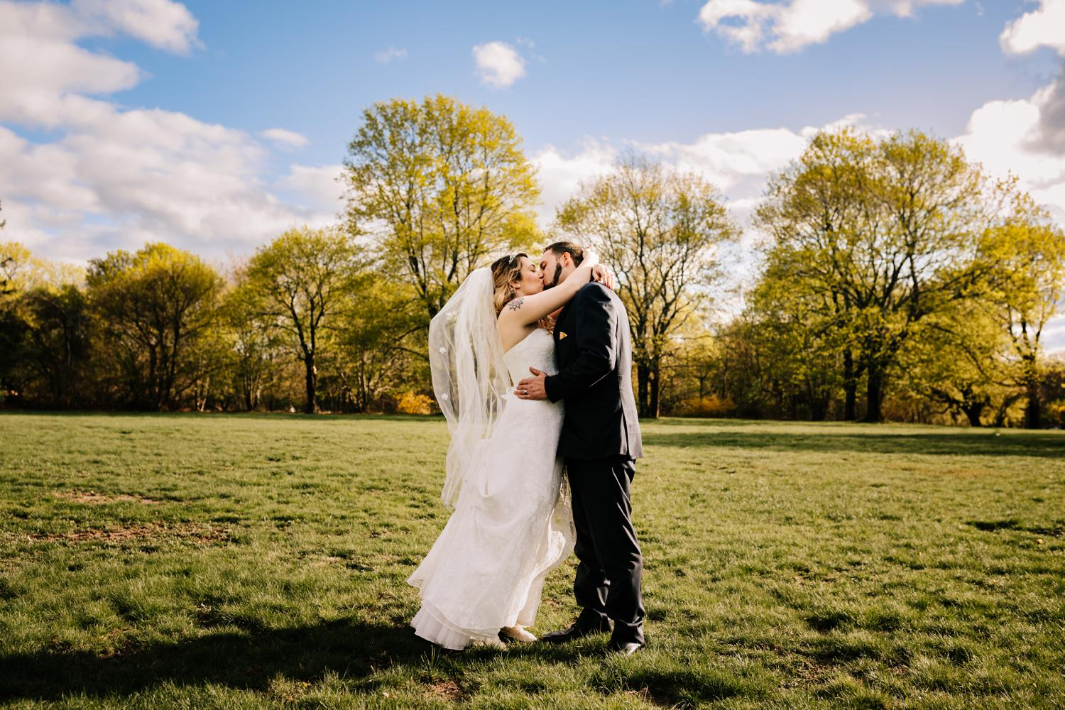 Tattooed bride and groom kissing at noon in field