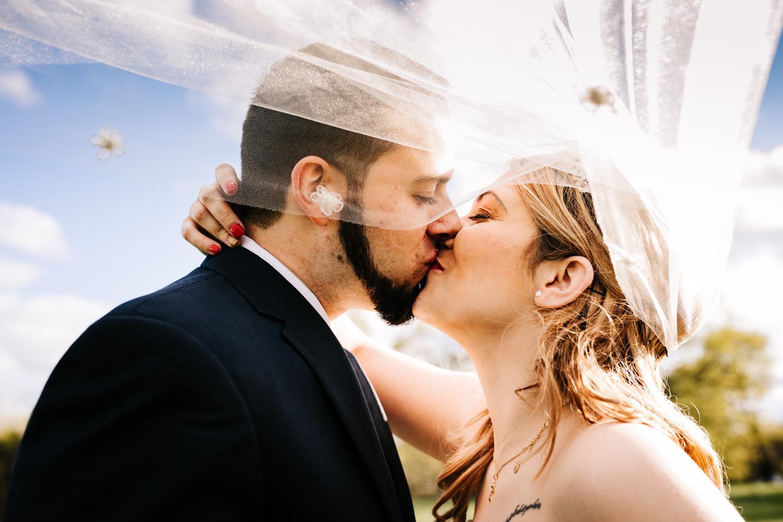 Tattoed wedding couple kissing under veil