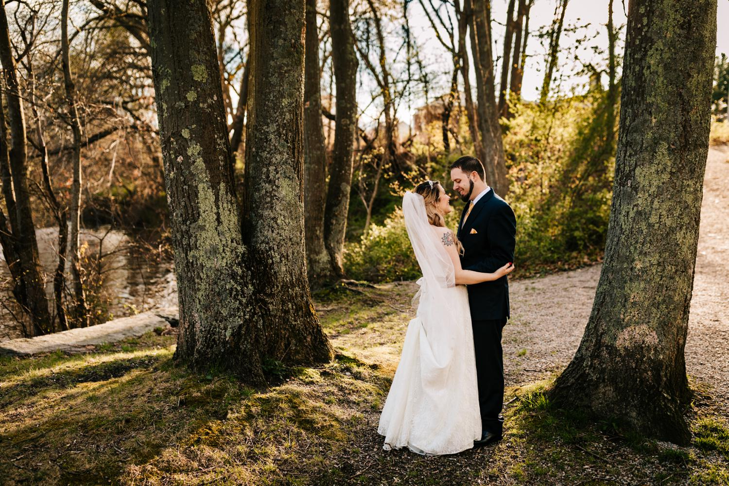 Bride and groom embracing in trees at park with tattoos