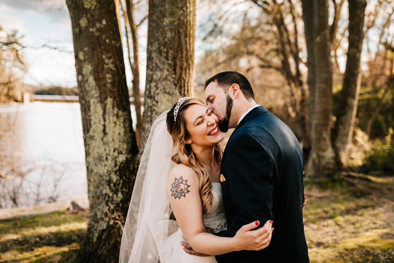 Groom kissing tattooed bride in woods at golden hour