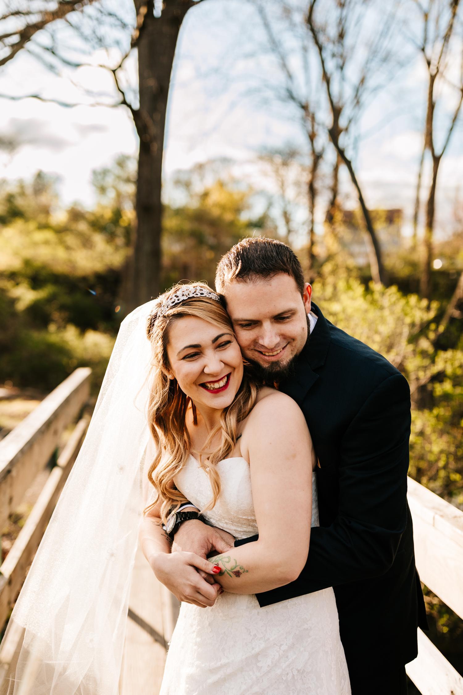 Groom hugging bride on bridge in woods
