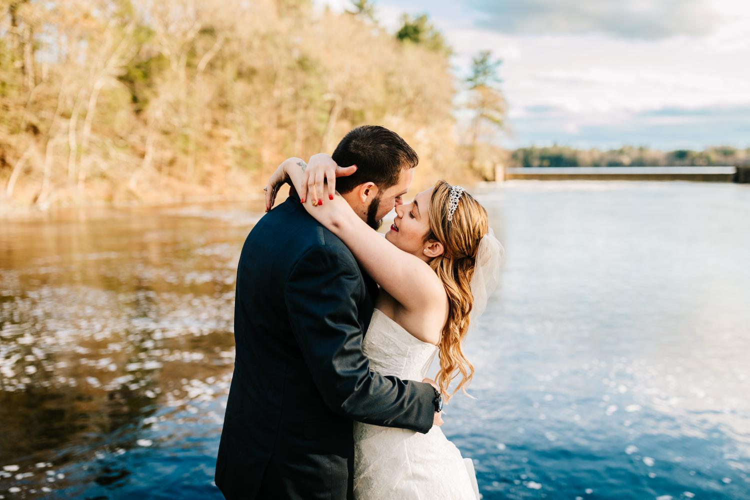 Tattooed bride and groom about to kiss at lake