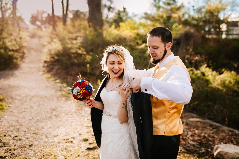 Groom giving jacket to tattooed bride