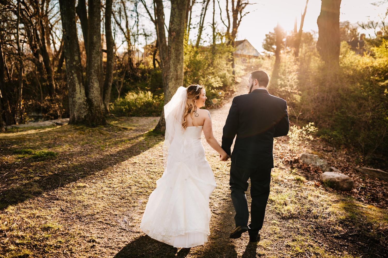 Tattooed bride and groom walking down trail