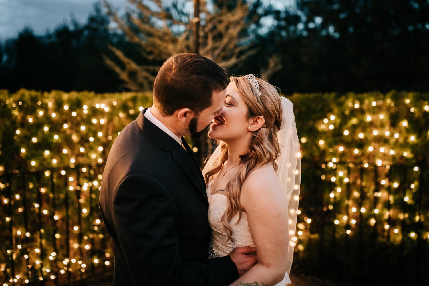Bride and groom surrounded by lights at night kissing