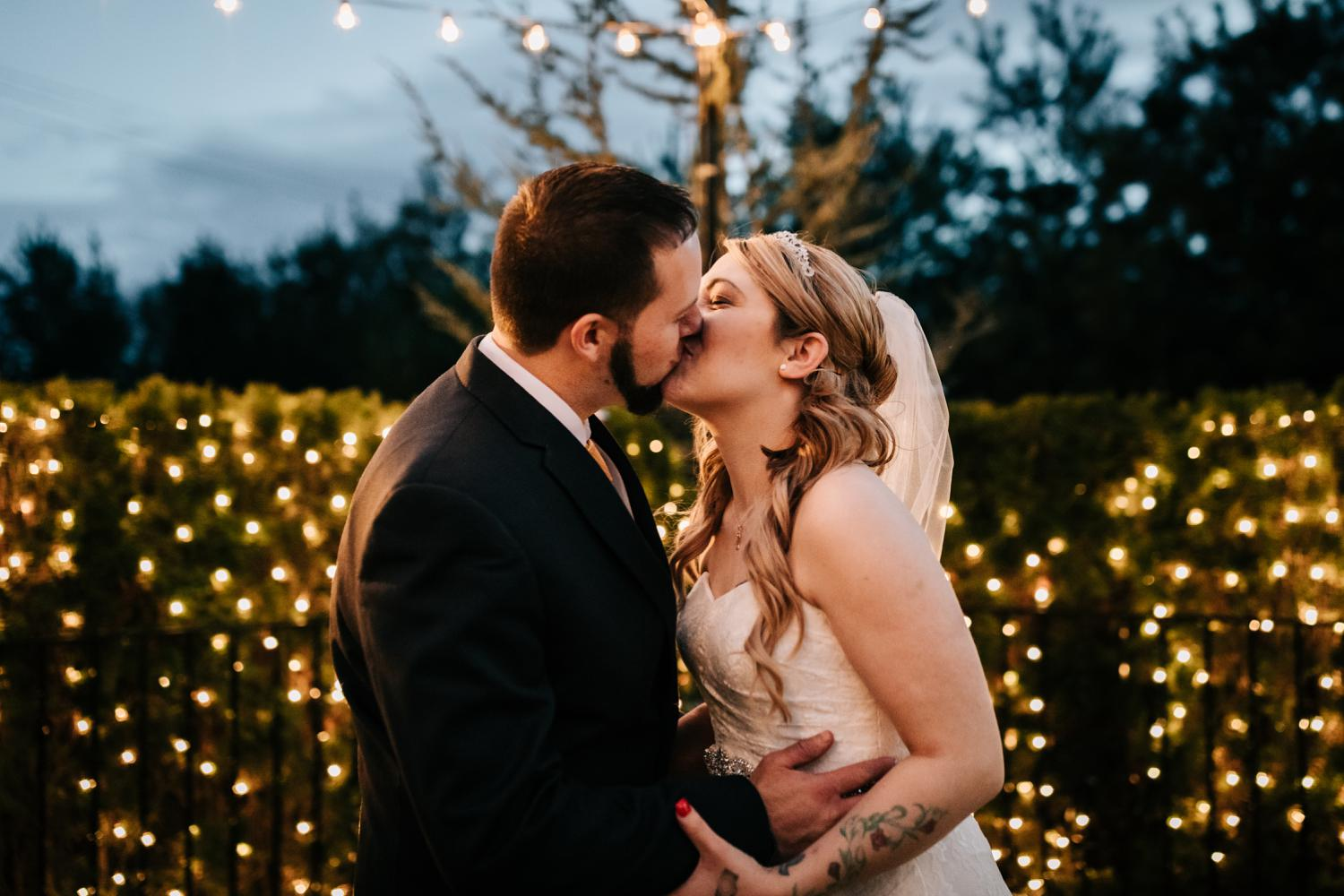Tattooed bride and groom kissing with twinkle lights