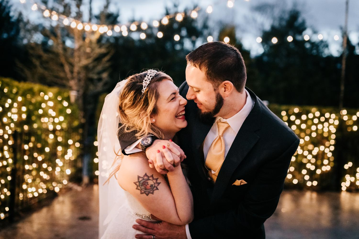 Bride and groom laughing and embracing under christmas lights at night