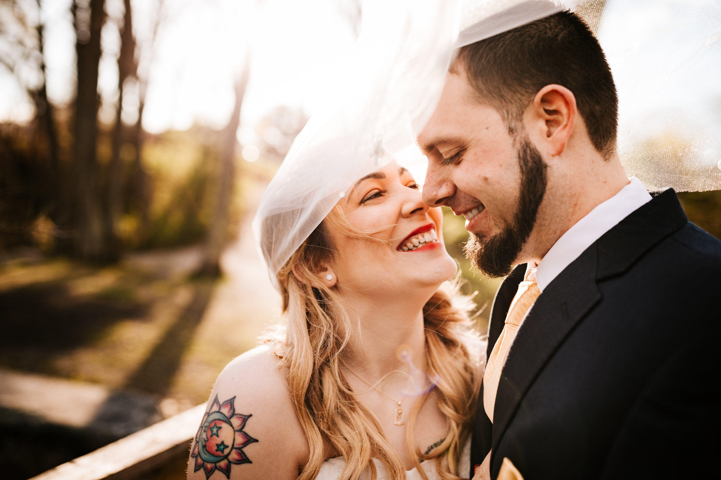 Smiling tattooed bride and groom under veil at golden hour