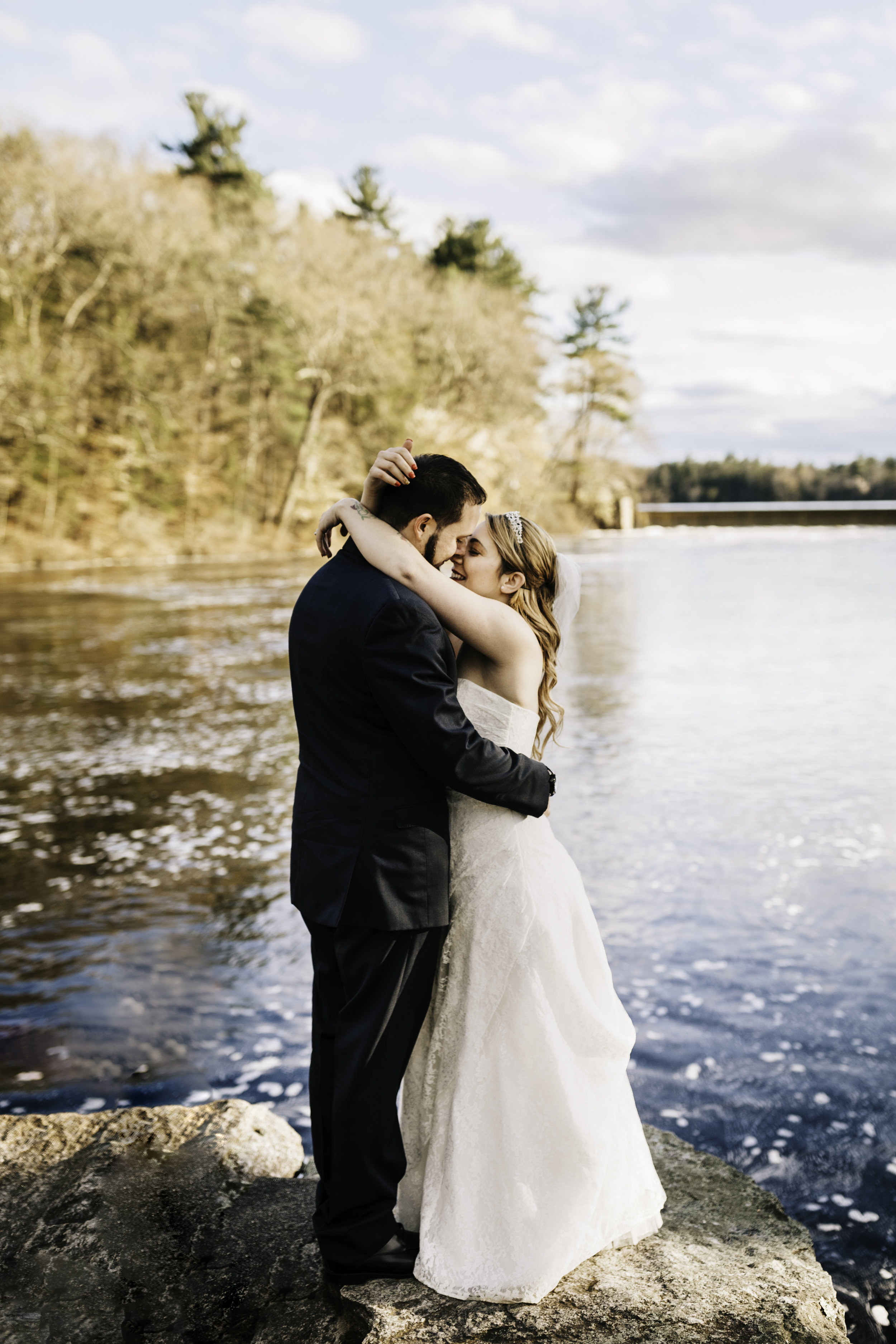 Bride and groom embracing at waterfront