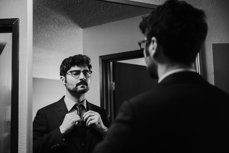 Groom putting on tie in mirror in Santa Fe hotel