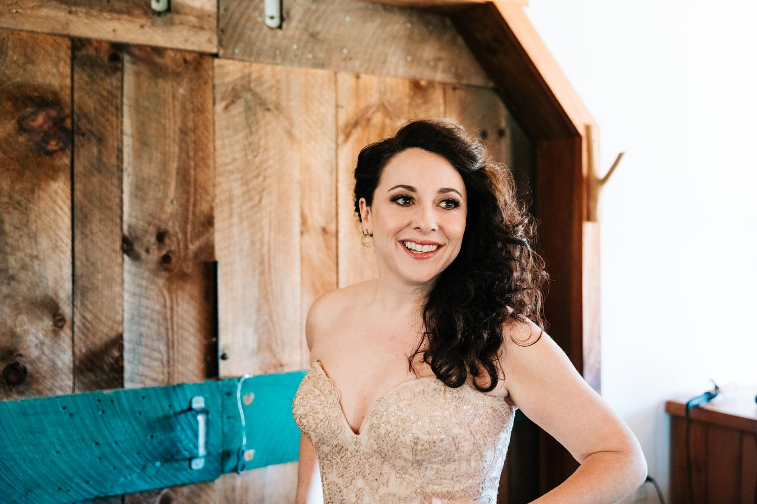 Bride smiling while putting on wedding dress in Santa Fe
