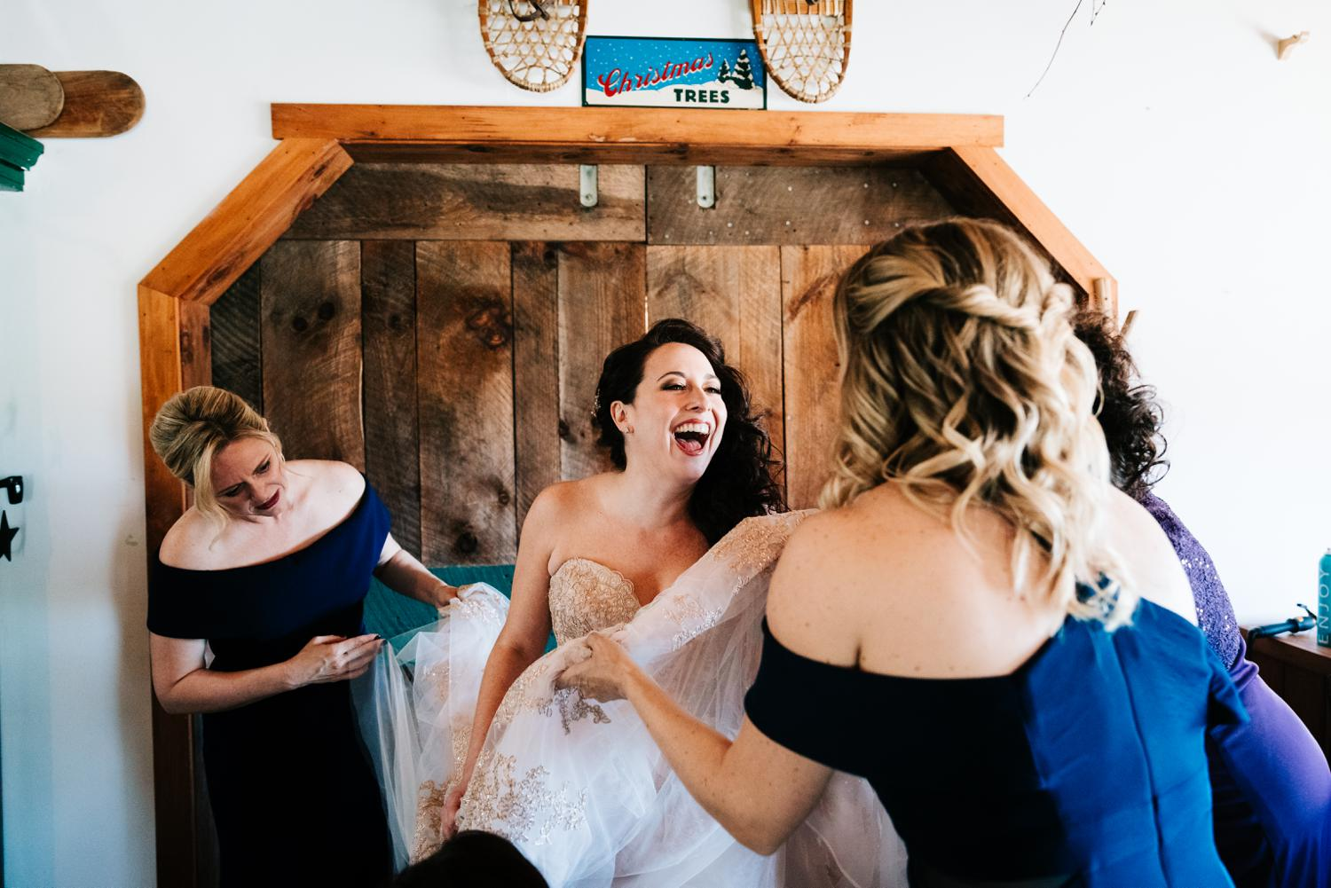 Bride laughing while putting on wedding dress in Albuquerque