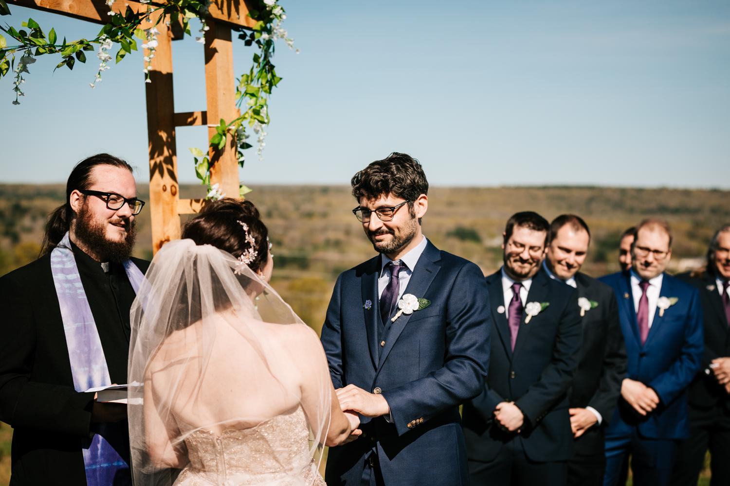 Groom looking at bride during ceremony under floral arch in New Mexico