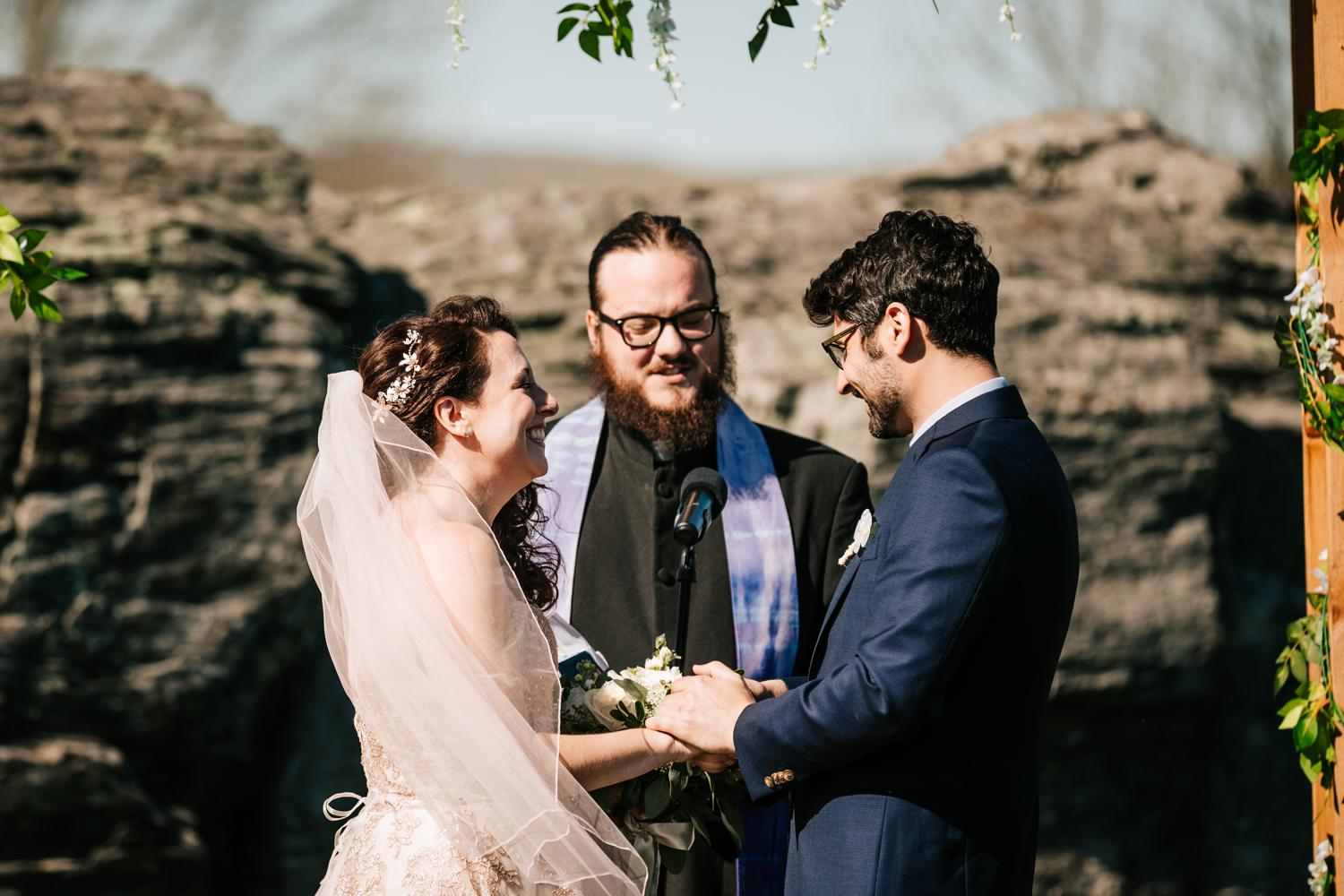 Bride and groom exchanging rings at outdoor wedding in Corrales