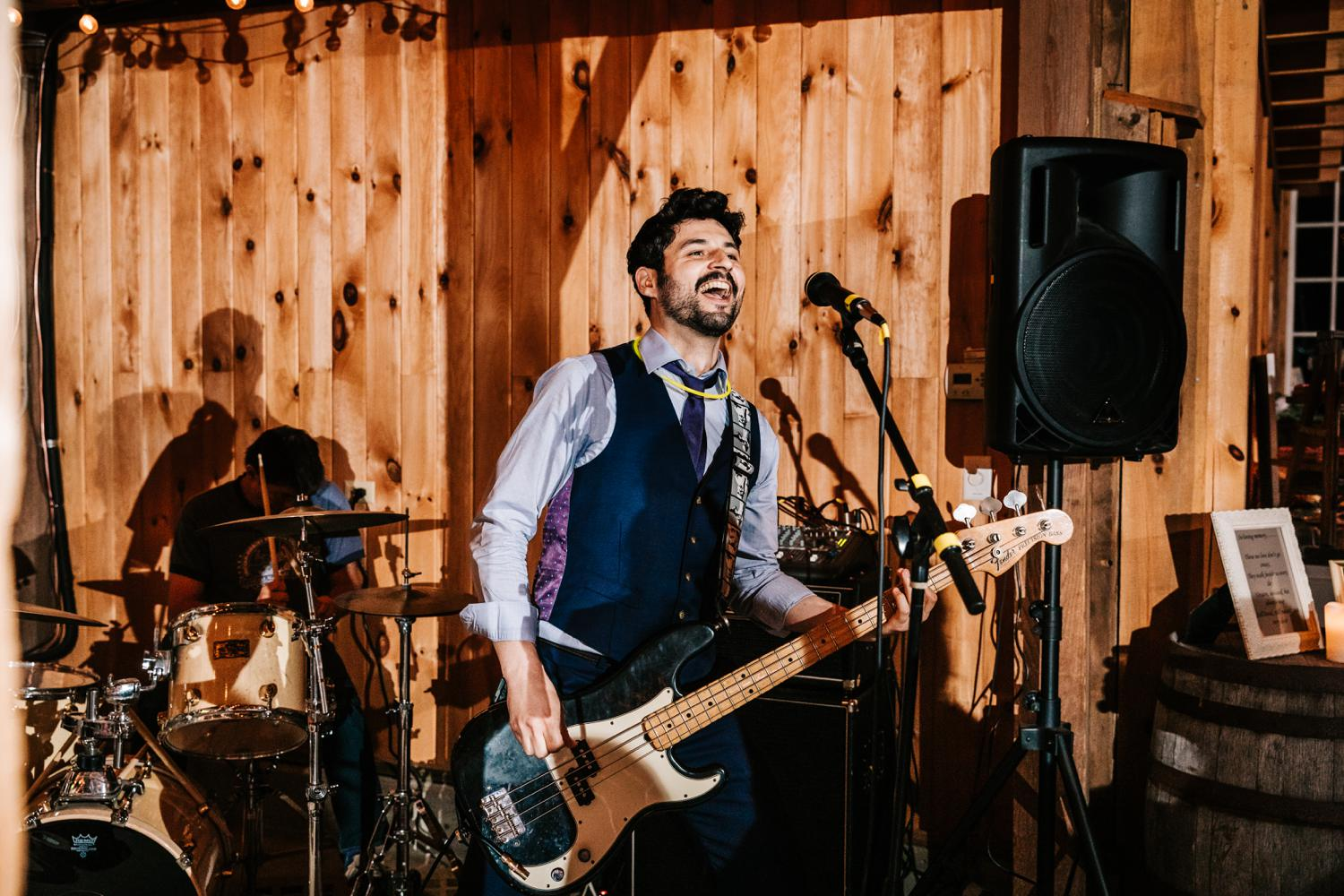 Groom playing guitar at music themed Albuquerque wedding reception