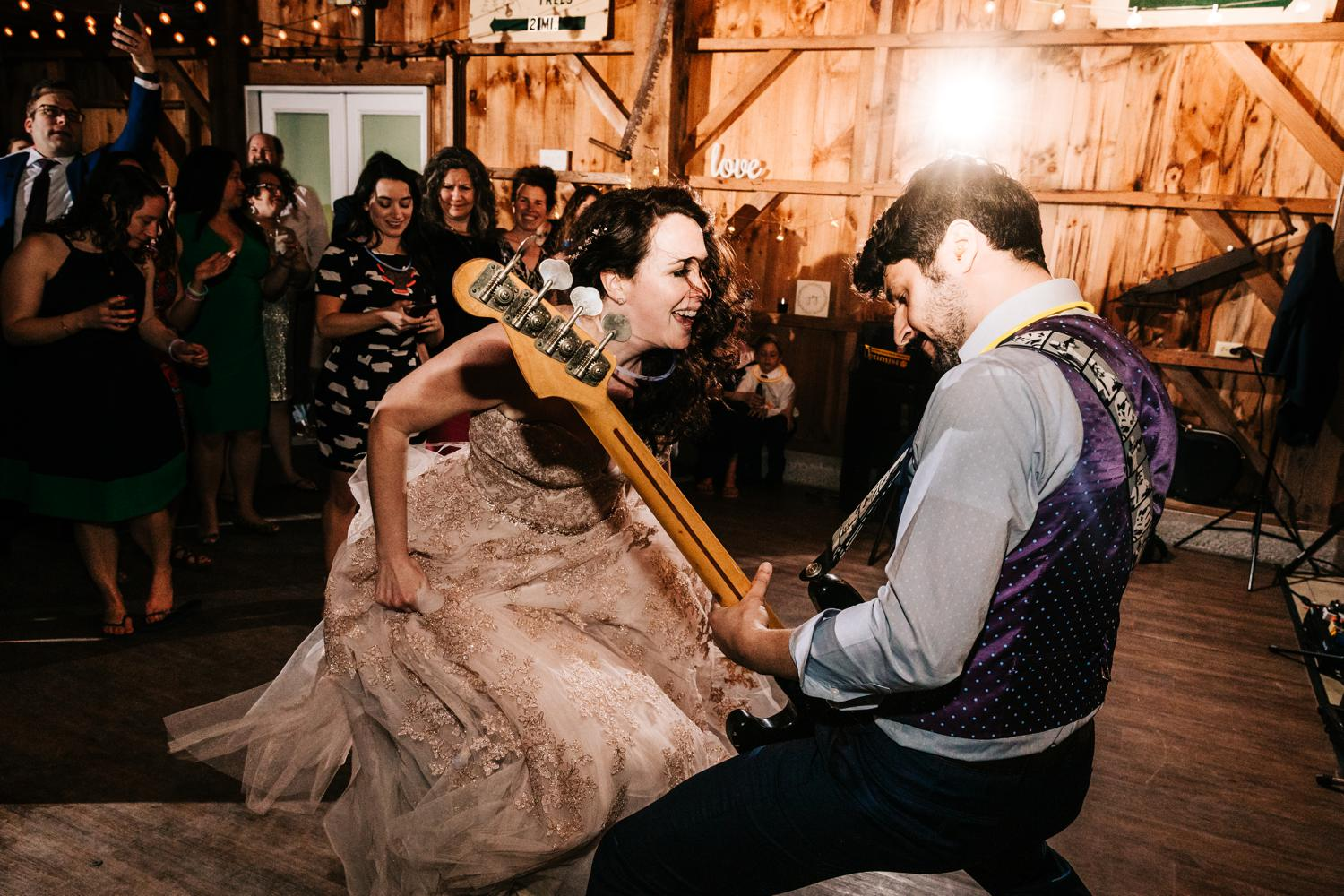 Bride and groom dancing and playing bass guitar in barn wedding in New Mexico