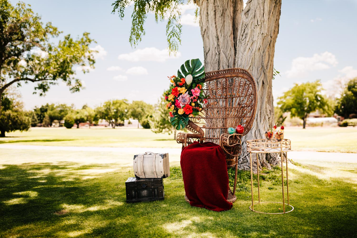 peacock chair with vibrant florals, suitcases, and blanket for Cuban style wedding in Albuquerque