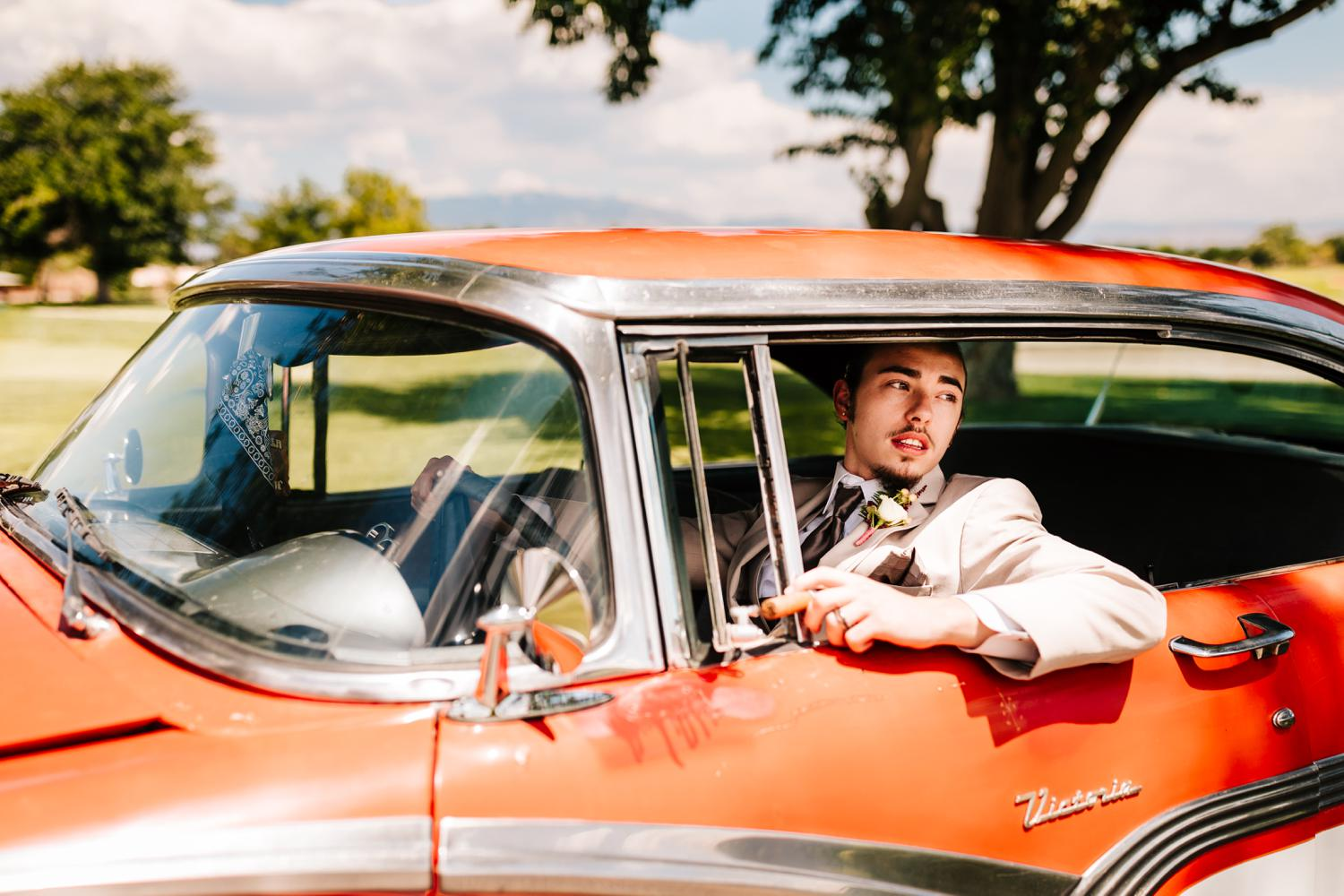 Groom in vintage red car on wedding day in Albuquerque, New Mexico