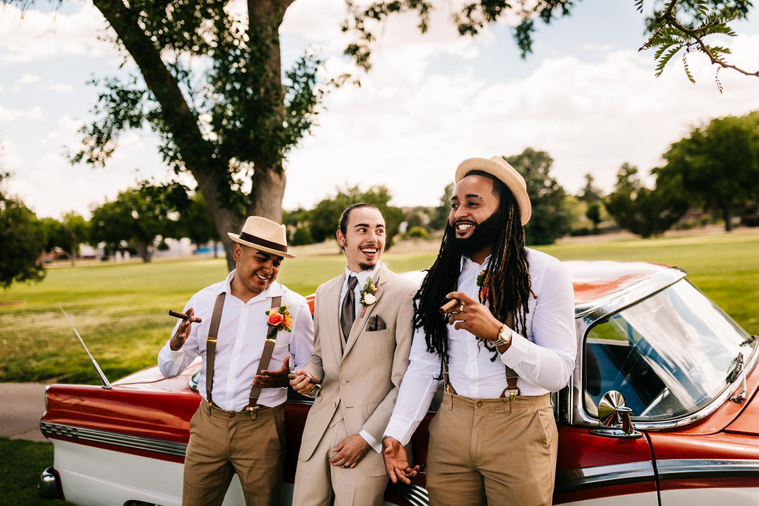 Groomsmen laughing with vintage car at tropical themed wedding in Albuquerque