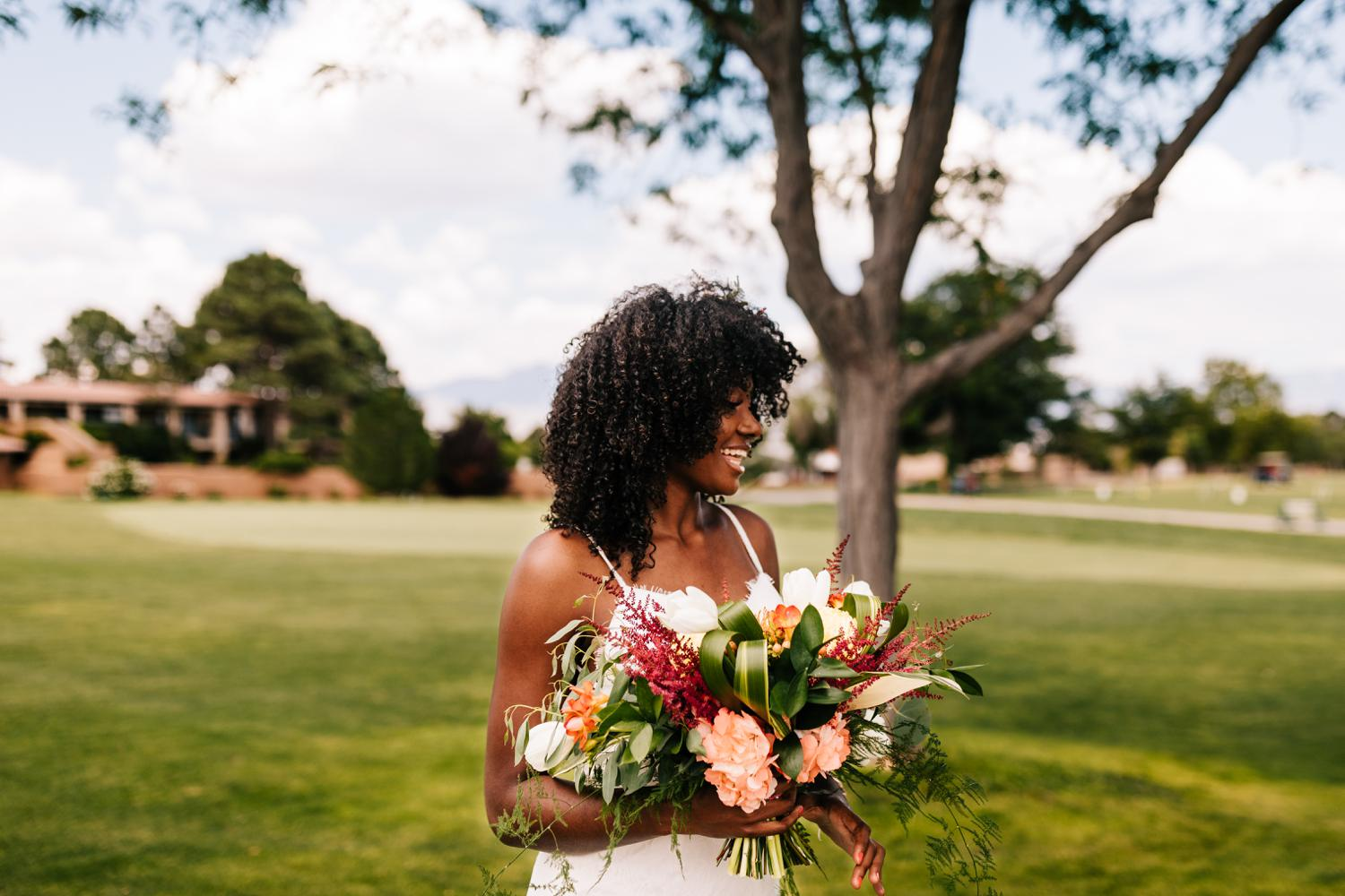 Smiling, happy bride with colorful bouquet in tropical themed Albuquerque wedding