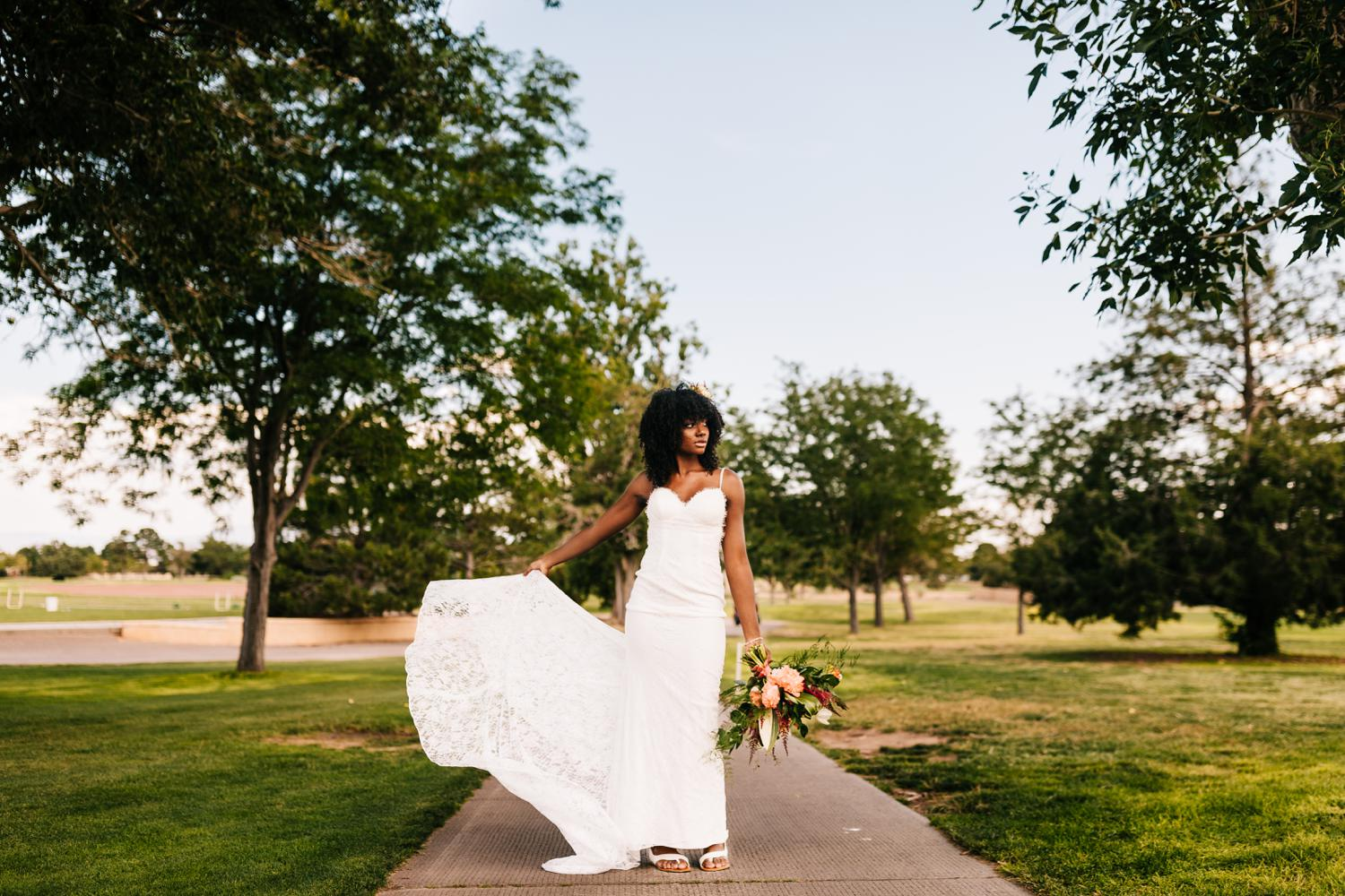 Bride flipping dress with vibrant flowers in tropical themed New Mexico Wedding