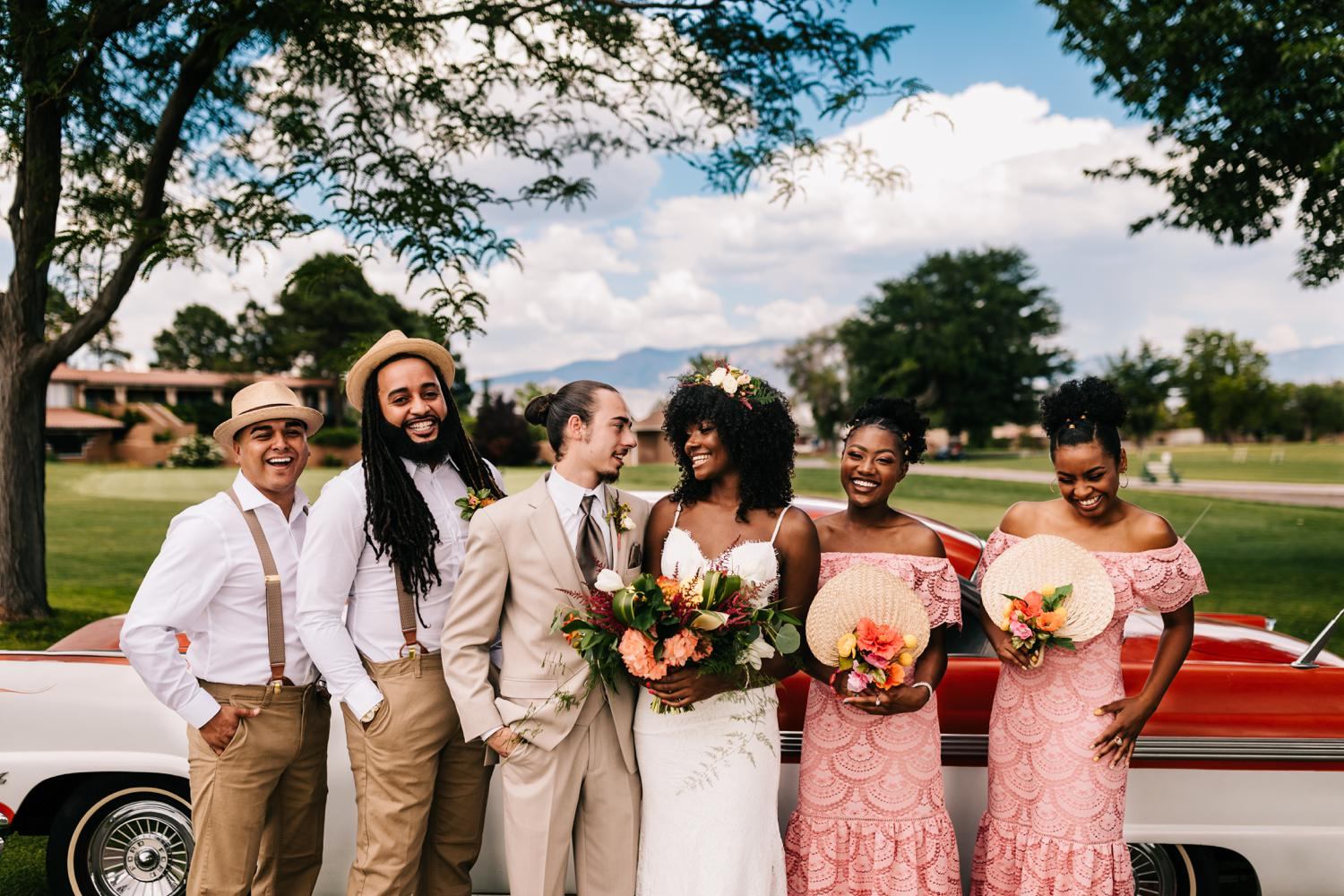 Colorful, laughing bridal party in front of Sandia Mountains, New Mexico