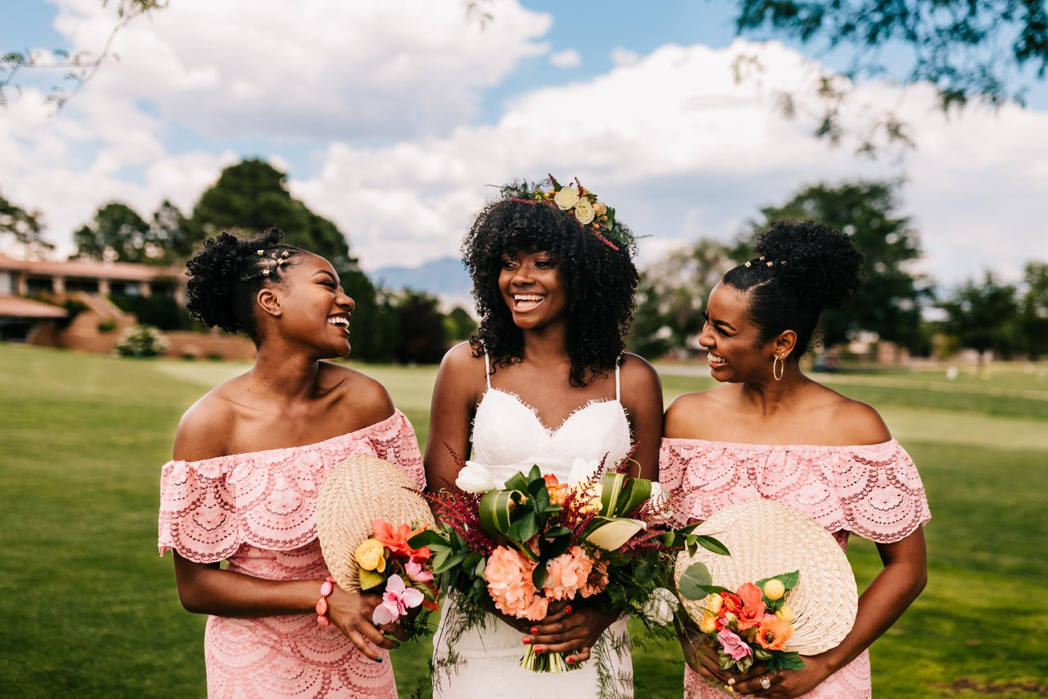 Bridesmaids wearing pink and holding vibrant bouquets and fans for Albuquerque wedding