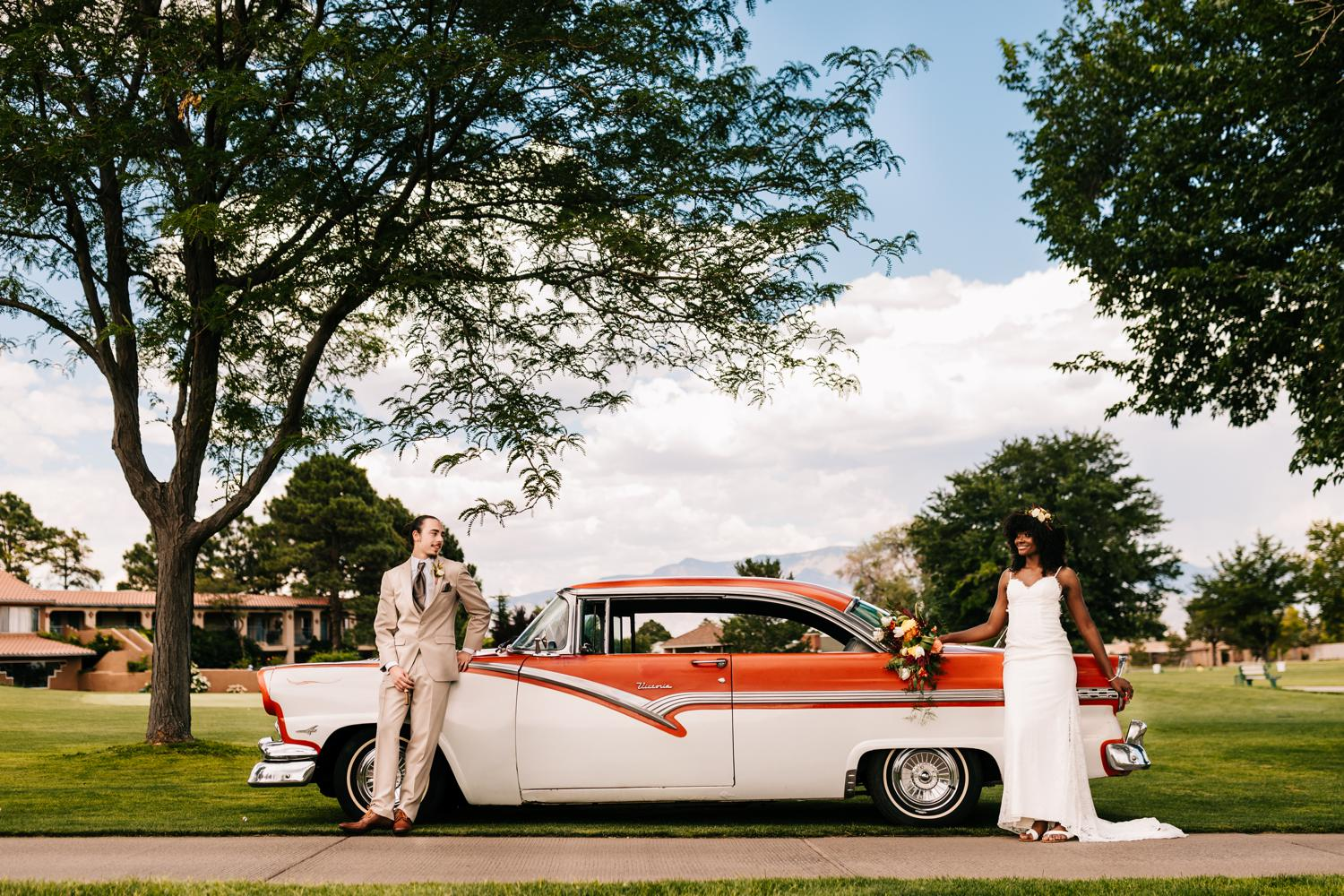 Bride and groom with vintage red car in Albuquerque