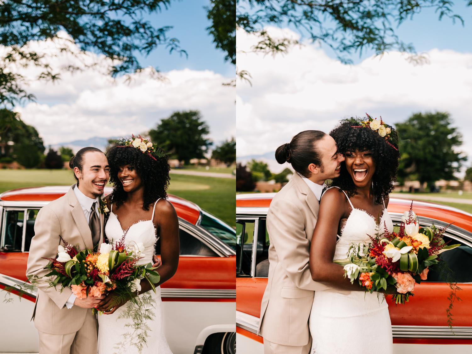 Playful bride and groom laughing with vibrant red car in New Mexico