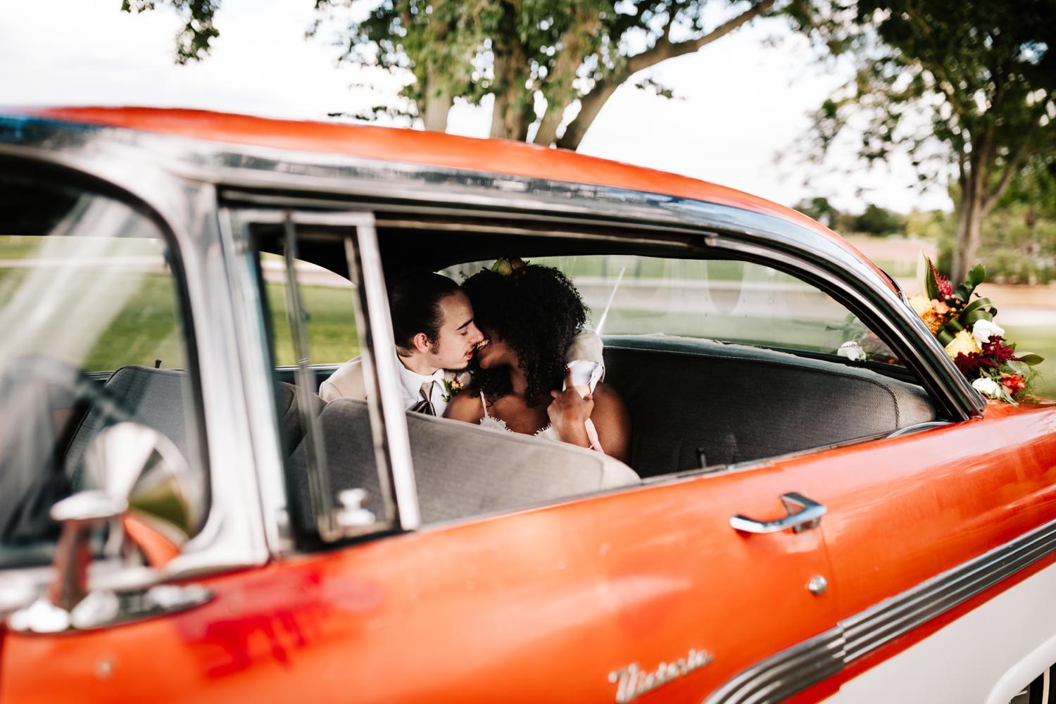 Bride and groom in vintage getaway car for tropical themed wedding in New Mexico