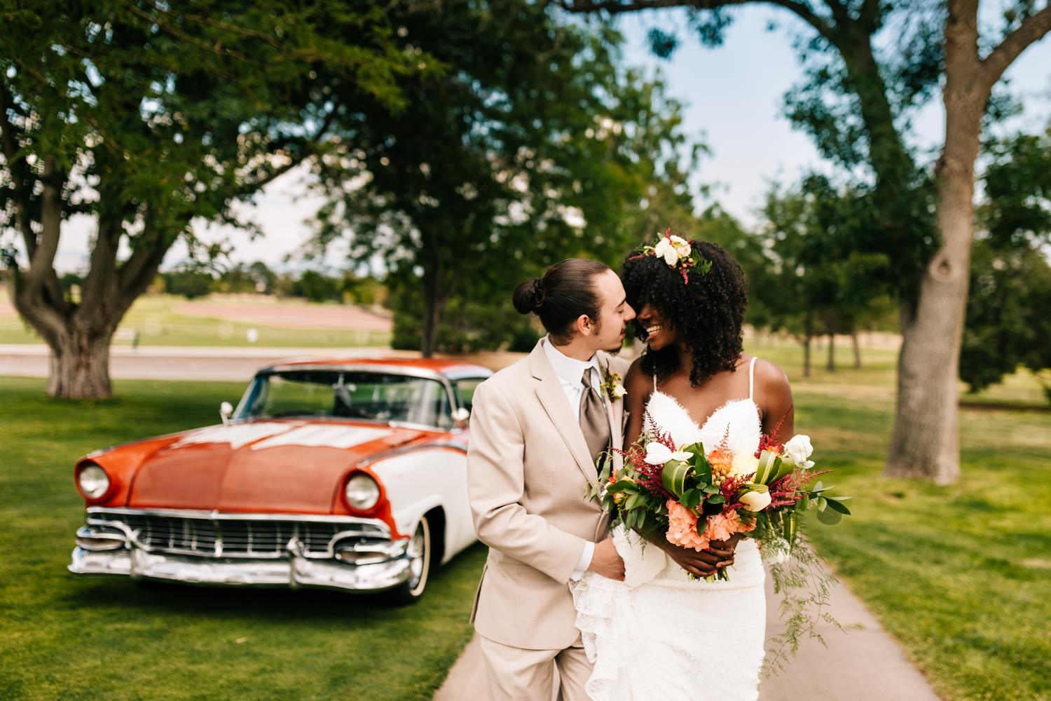Bride and groom walking away from vintage car at a New Mexico wedding