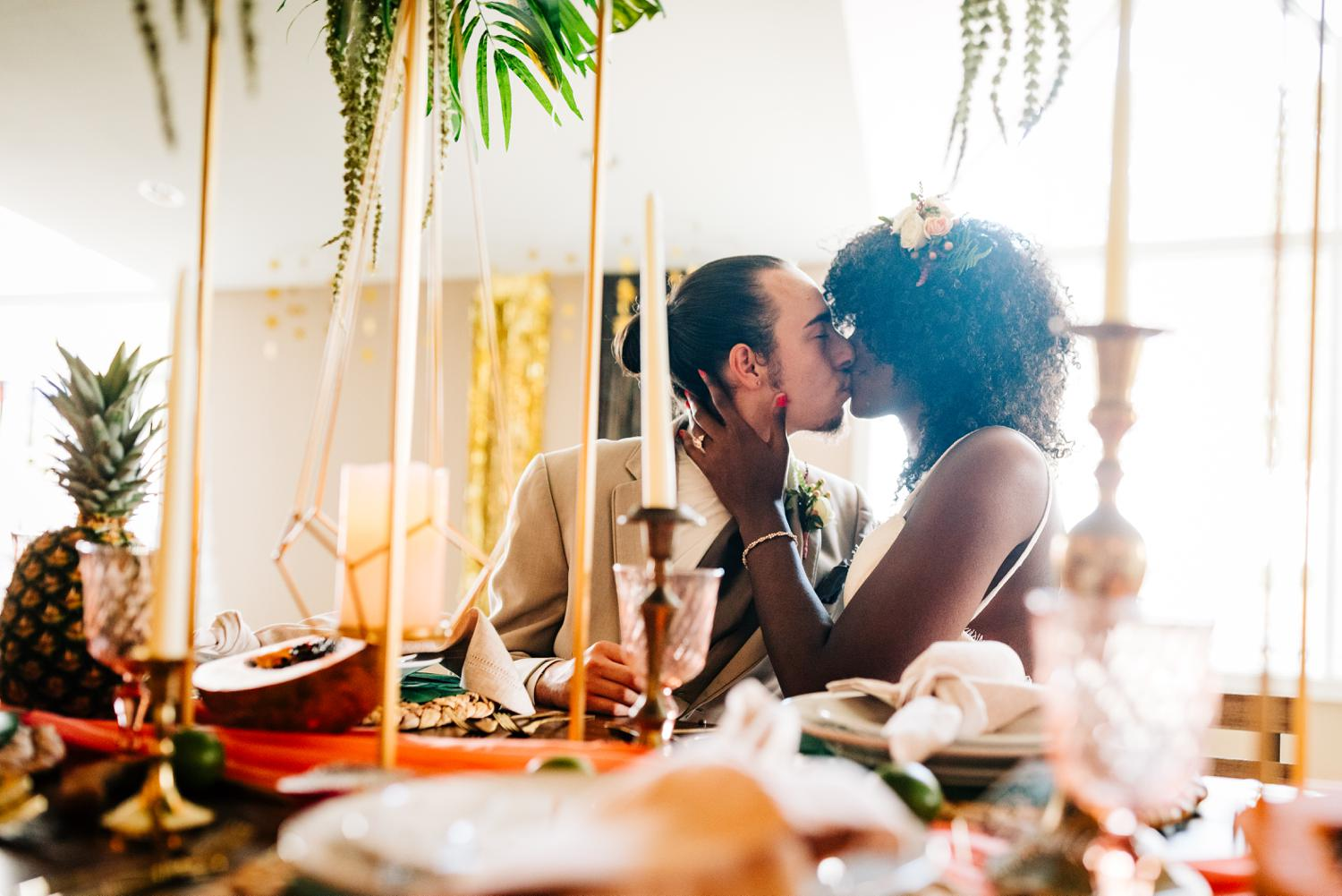 Bride and groom kiss at elaborate, colorful table in Albuquerque wedding