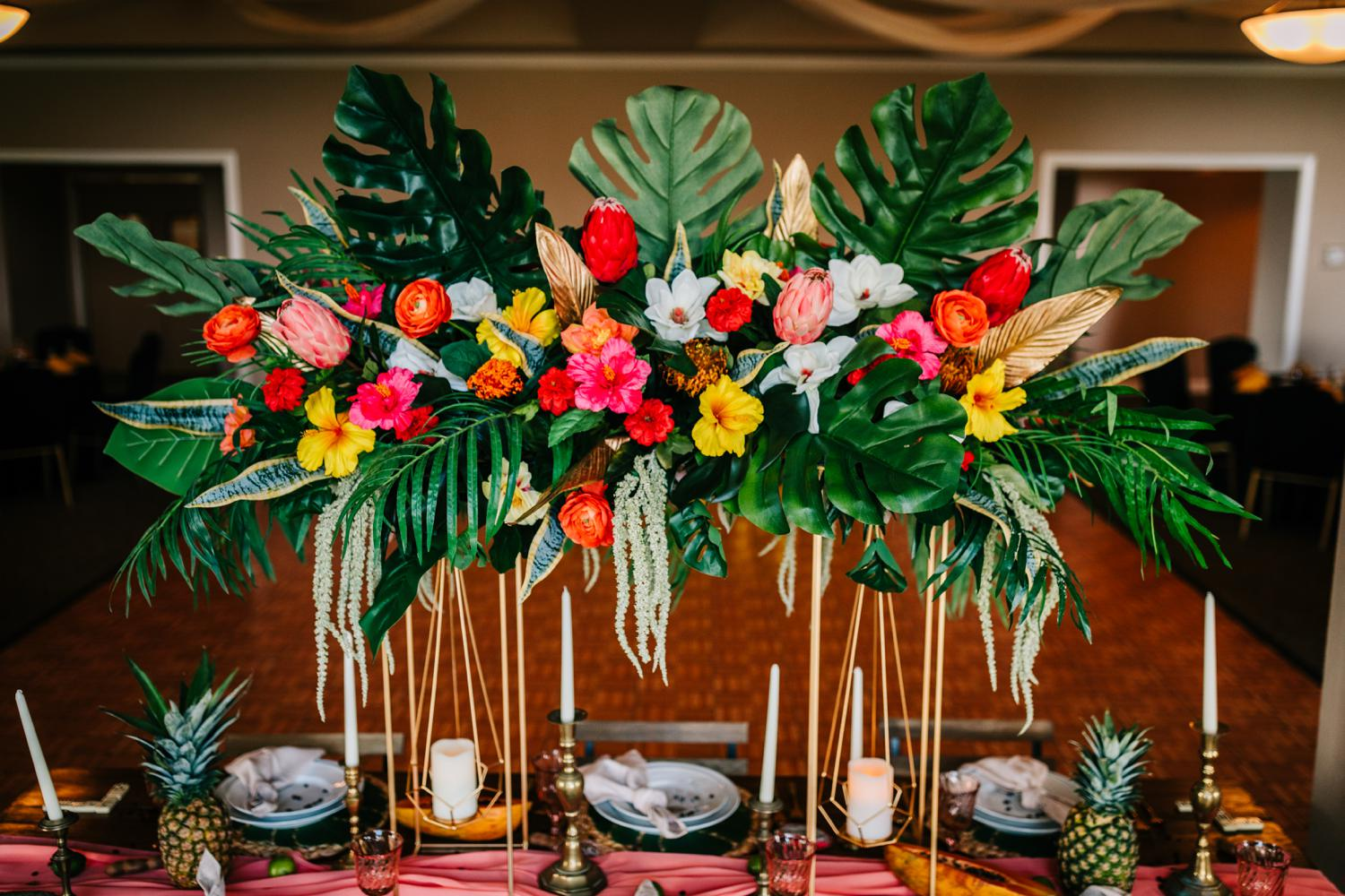 Vibrant, colorful, leafy centerpiece for tropical themed wedding in New Mexico