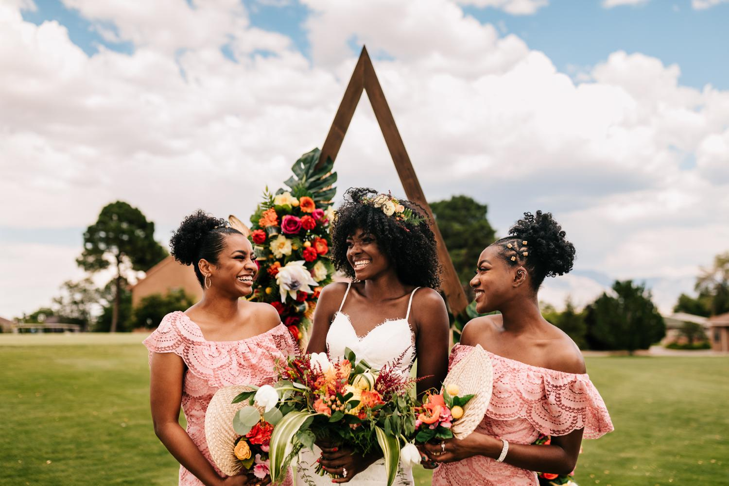 Bridesmaids holding flower fan bouquets and laughing under flower arch in New Mexico