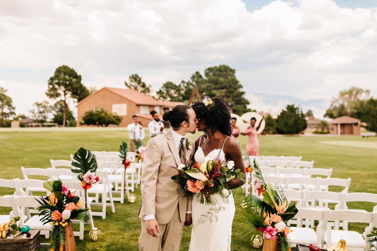 Bride and groom walk up the aisle for tropical themed wedding ceremony in Albuqueque, New Mexico