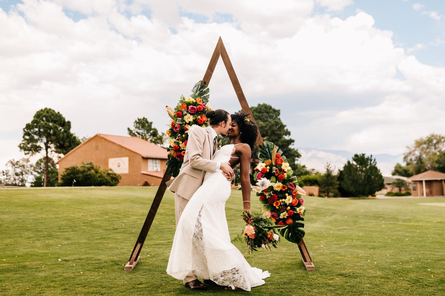 Bride and groom first kiss at Paradise Hills Golf Club, Albuquerque, New Mexico