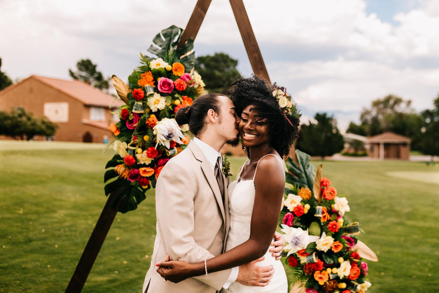 Groom kissing bride under wooden ceremony arch in front of Sandia Mountains
