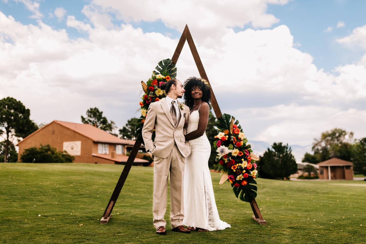 Bride and groom posing under flower arch at Sandia Mountains, New Mexico