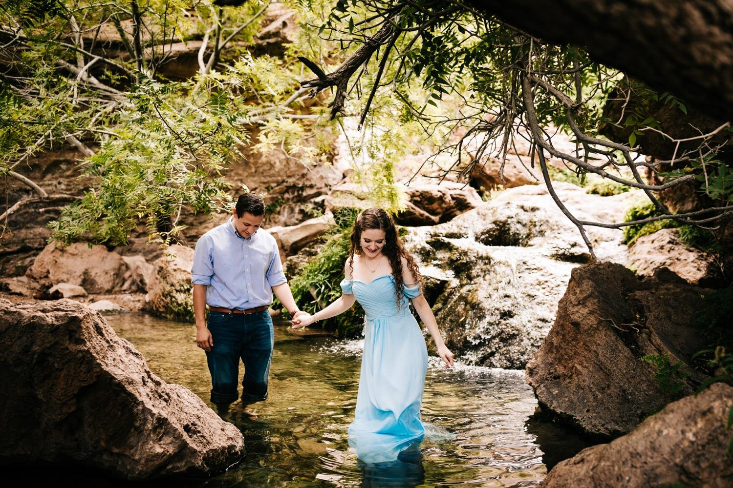 Couple walks through stream during their engagement session in Carlsbad, New Mexico