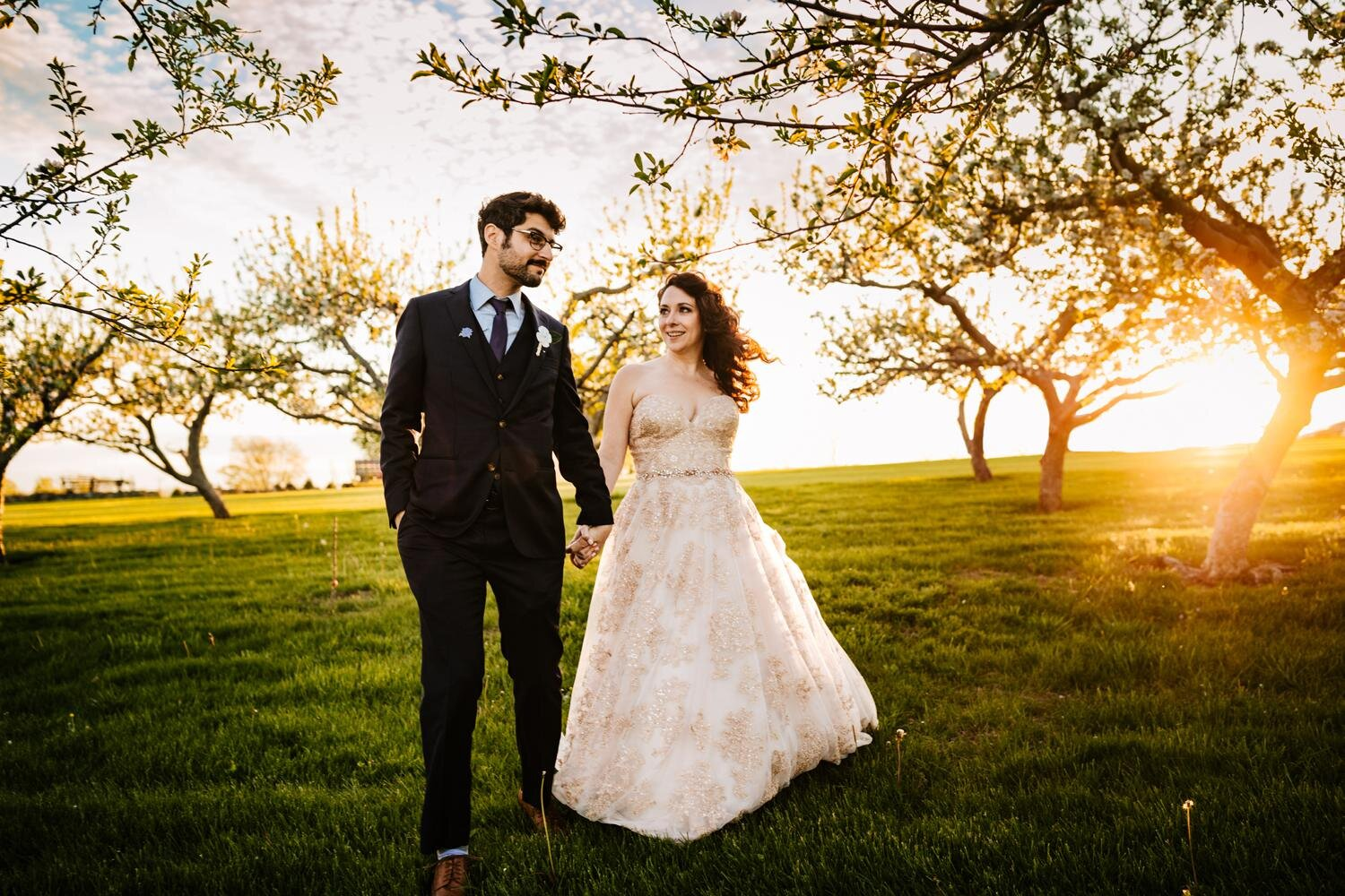 bride and groom holding hands and running through a field in New Mexico