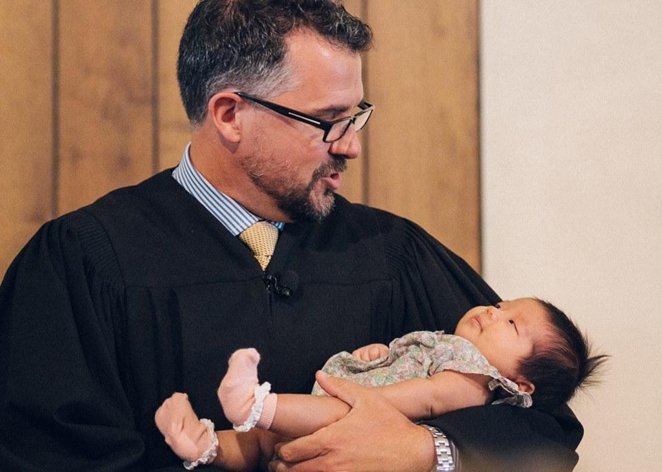 Rev. Michael Brown botezând un copil nou născut într-o familie de credincioși din  Biserica Reformată Unită din San Diego.