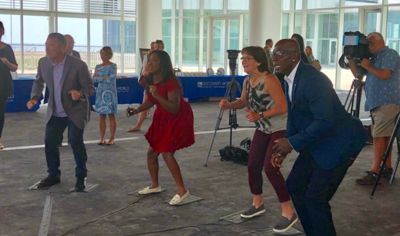 (From left) Milwaukee attorney Jason Abraham, Melinda Davenport of WISN-TV (Channel 12), Olympic speedskater Bonnie Blair and former Green Bay Packers wide receiver Donald Driver test out a virtual reality sausage race game.