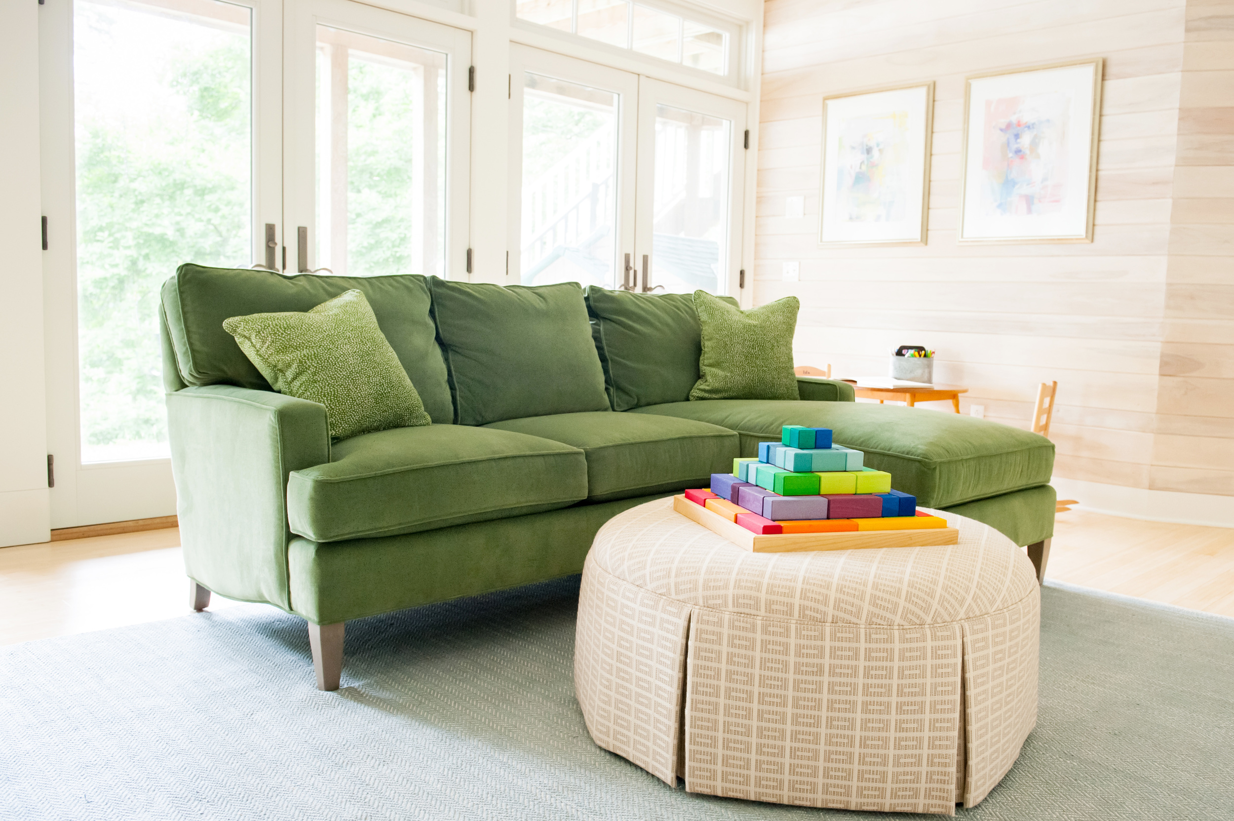 green_couch_and_large_windows