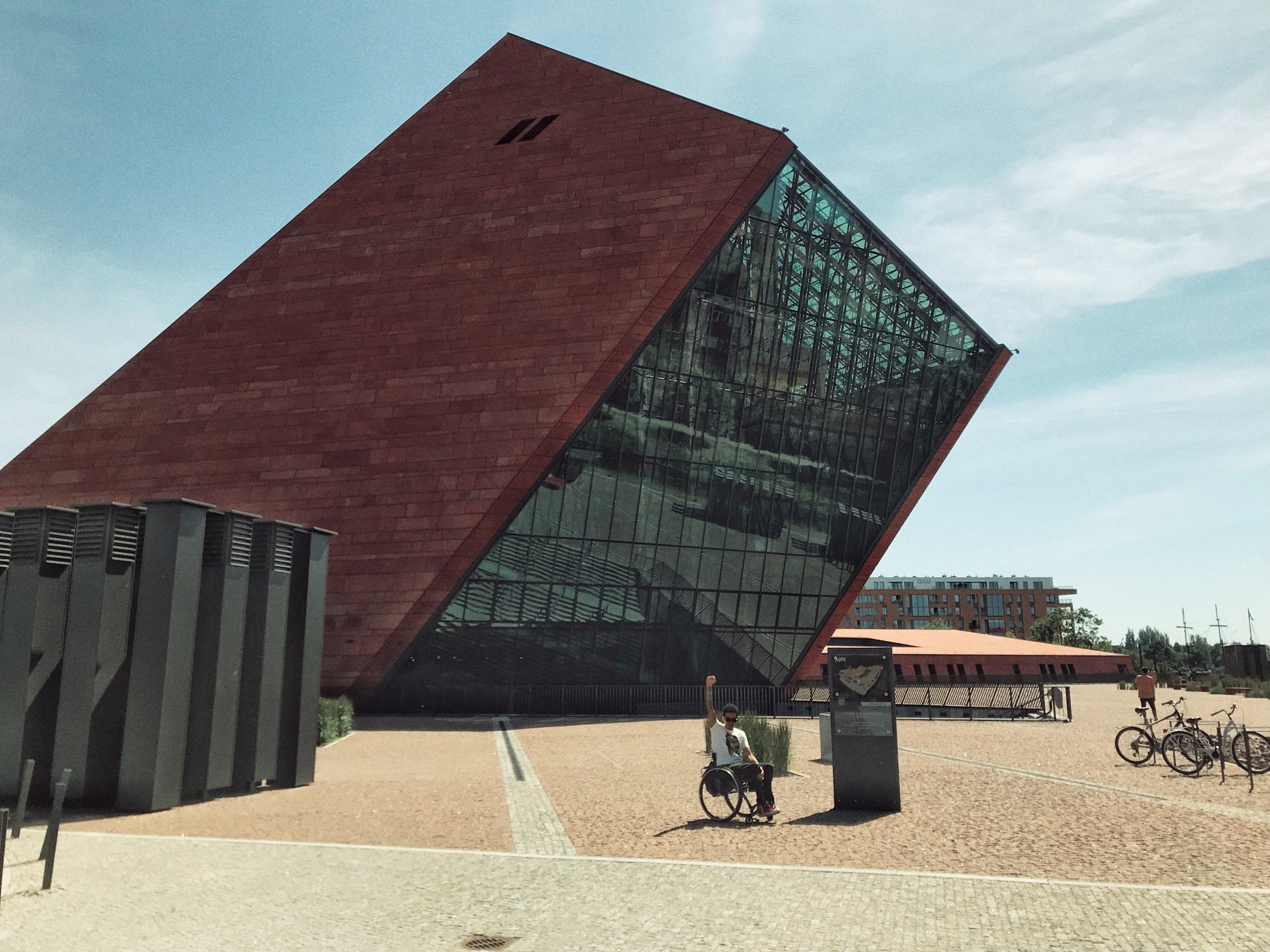 An angled tower wrapped in red concrete panels and glazing contains the entrance to this Second World War Museum which is mostly housed beneath the surface of a public plaza in the Polish city of Gdansk.