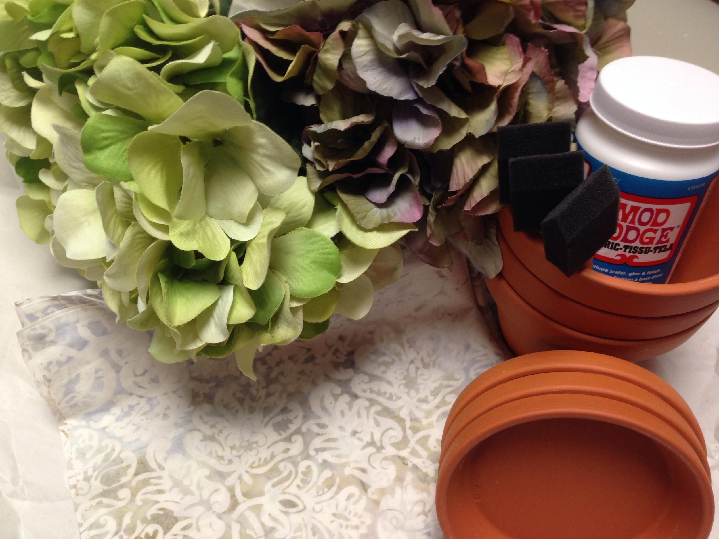All your supplies needed to modge podge terracotta pots.
